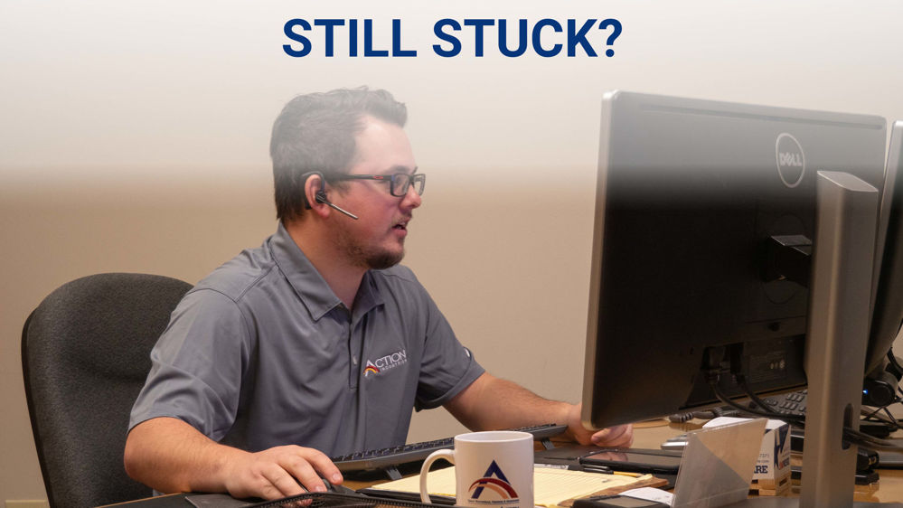 Action Industries sales and support member at a desk on the phone discussing garage door parts